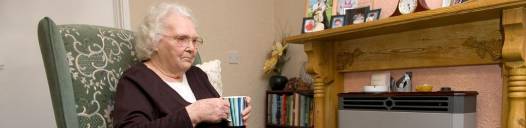 Older lady in armchair drinking tea in front of gas fire